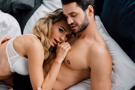 Photo pour Sexy woman with finger near mouth looking at camera near muscular boyfriend on bed - image libre de droit