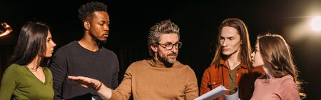 Photo pour panoramic shot of multiethnic actors and actresses rehearsing with theater director on stage - image libre de droit