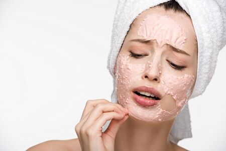 Photo pour displeased girl removing peeling mask from face isolated on white - image libre de droit