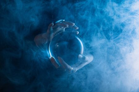 Photo pour Partial view of witch holding crystal ball with smoke around on dark blue  - image libre de droit