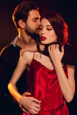 Foto de Handsome man embracing and kissing elegant girlfriend in red dress isolated on black - Imagen libre de derechos