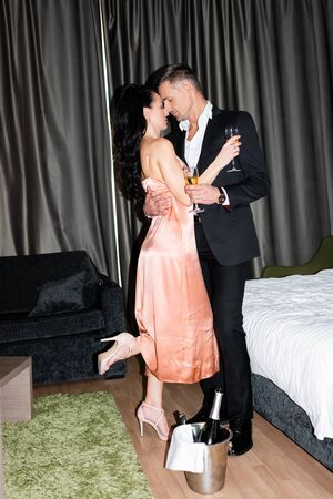 Photo pour side view of boyfriend and girlfriend holding glasses and kissing in hotel - image libre de droit