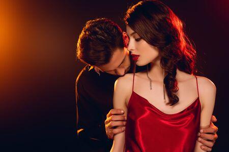 Foto de Man kissing shoulder of elegant girlfriend on black background with lighting - Imagen libre de derechos