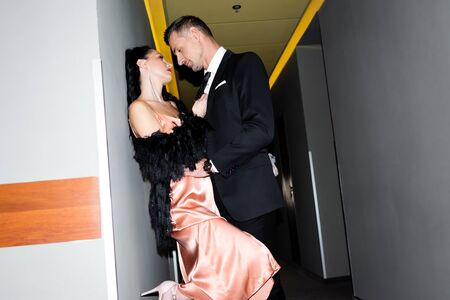 Photo pour side view of boyfriend and girlfriend kissing and hugging in hotel - image libre de droit