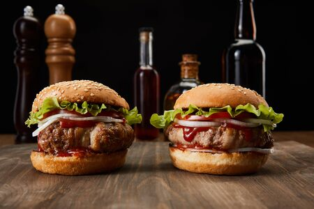 Foto de selective focus of two burgers on wooden surface near oil, vinegar and beer bottles, pepper and salt mills isolated on black - Imagen libre de derechos