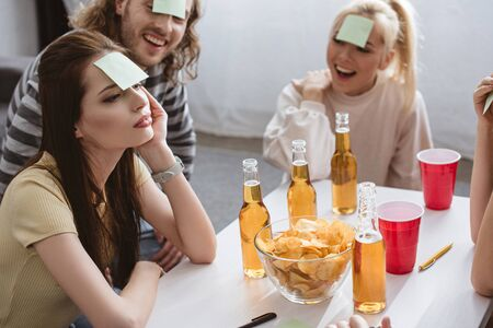 Photo for thoughtful girl playing name game with cheerful friends with sticky notes on foreheads - Royalty Free Image