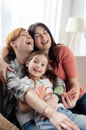 Photo for Selective focus of same sex parents laughing while embracing daughter on couch in living room - Royalty Free Image