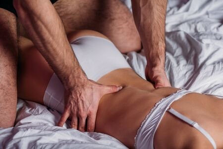 Photo for cropped view of man making back erotic massage to sexy girl in white underwear lying in bed - Royalty Free Image