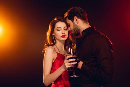 Foto de Handsome man holding glass of red wine near elegant girlfriend on black background with lighting - Imagen libre de derechos