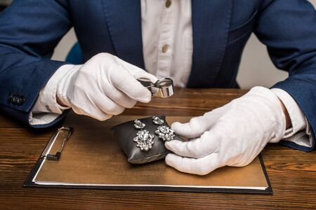 Photo pour Cropped view of jewelry appraiser holding magnifying glass and earnings on board on table isolated on grey - image libre de droit