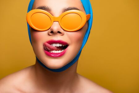 Photo pour happy girl in scarf and fashionable sunglasses licking lip, isolated on yellow - image libre de droit
