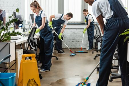 Photo pour multicultural team of young cleaners washing floor with mops in office - image libre de droit