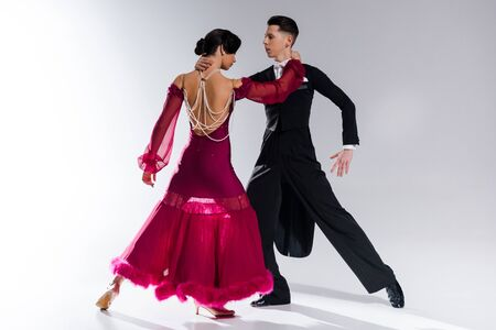Photo pour elegant young couple of ballroom dancers in red dress in suit dancing on white - image libre de droit