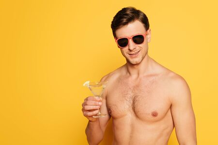 Photo pour shirtless man in sunglasses holding glass of cocktail on yellow background - image libre de droit