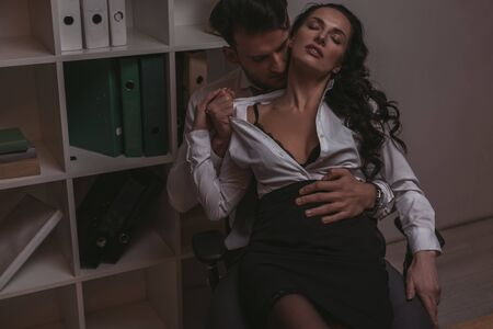 Photo for handsome businessman undressing seductive secretary while sitting on office chair together - Royalty Free Image