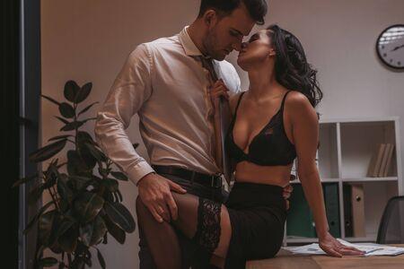 Photo pour handsome businessman in formal wear touching leg of seductive secretary in lingerie - image libre de droit
