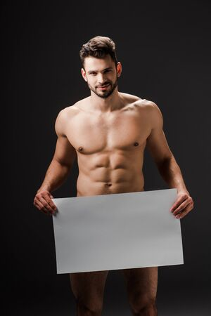 Photo for happy sexy naked man holding blank placard isolated on black - Royalty Free Image