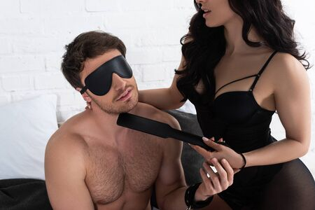 Photo for Woman pointing with spanking paddle at man with blindfold - Royalty Free Image