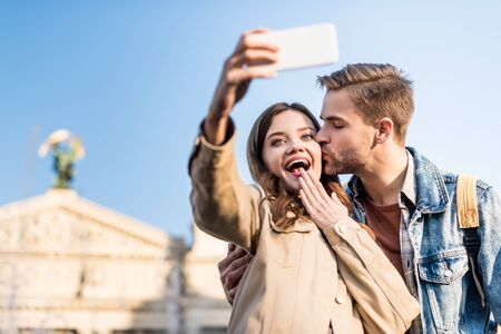 Photo pour Selective focus of man kissing excited girlfriend taking selfie with smartphone - image libre de droit