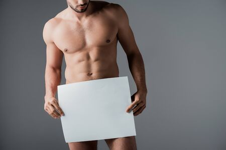 Photo for cropped view of sexy naked man holding empty board isolated on grey - Royalty Free Image