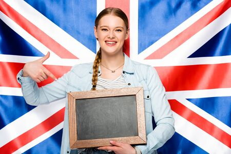 smiling pretty girl with braid pointing at empty chalkboard on uk flag background