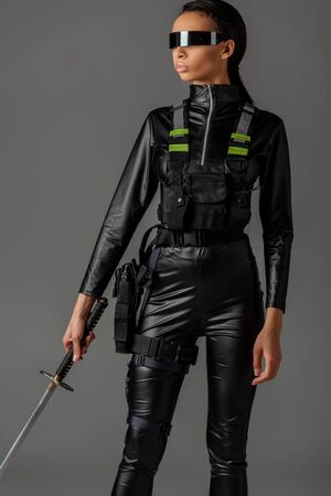 Photo pour attractive futuristic african american woman in glasses with sword isolated on grey - image libre de droit