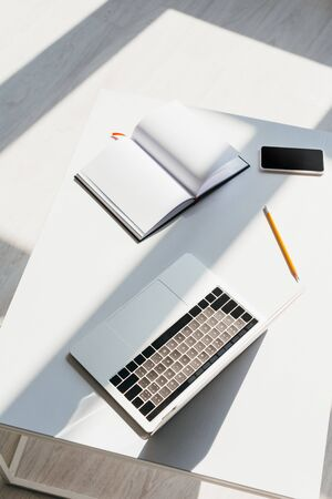 Photo for empty workplace with laptop, smartphone, notepad and pencil - Royalty Free Image