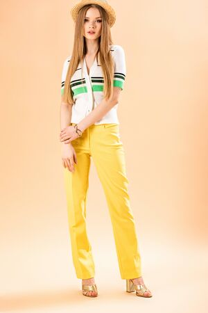 Photo for stylish girl posing in yellow trousers, polo and straw hat on beige - Royalty Free Image