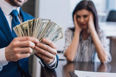 Photo pour Selective focus of collector with money near stressed woman at table in room - image libre de droit
