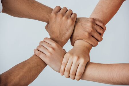 Photo pour Cropped view of multiethnic men doing unity gesture isolated on grey - image libre de droit