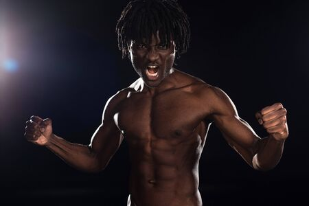 Photo pour muscular emotional african american man shouting on black with back light - image libre de droit