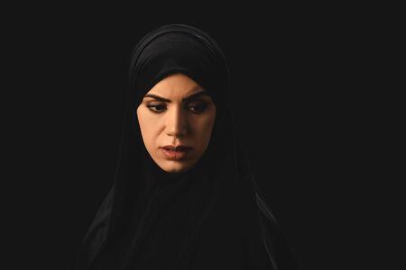 Photo pour Sad muslim woman looking away isolated on black - image libre de droit