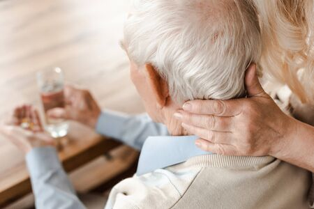 Photo pour ill elderly couple with pills and glass of water at home on self isolation, selective focus - image libre de droit