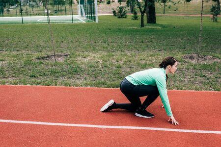 Foto de Side view of sportswoman in starting position on running path in park - Imagen libre de derechos