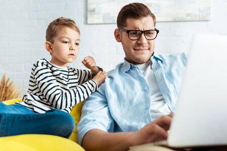 Photo pour cute child sitting near attentive father using laptop - image libre de droit