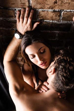 Photo pour Overhead view of shirtless man kissing seductive woman near brick wall - image libre de droit