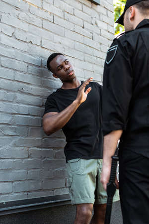 Photo pour selective focus of scared african american man with raised hand looking at policeman with baton, racism concept - image libre de droit
