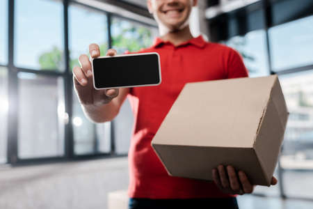 Foto für cropped view of happy delivery man holding smartphone with blank screen and carton box - Lizenzfreies Bild