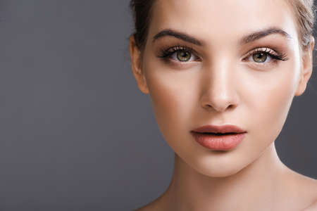 Photo pour beautiful young woman with makeup looking at camera isolated on grey - image libre de droit
