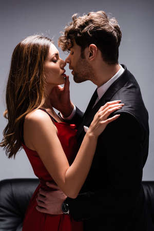 Photo pour Side view of handsome man in suit touching lips of beautiful woman in red dress near couch on grey - image libre de droit