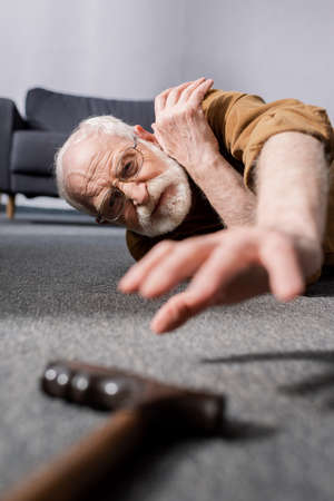 selective focus of powerless senior man lying on floor and trying to get walking stick