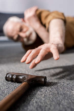 selective focus of helpless senior man lying on floor and trying to get walking stick