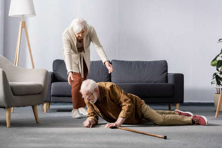 senior woman helping to get up fallen husband lying on floor near walking stick