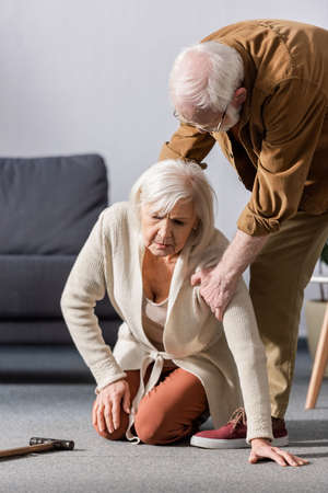 senior man helping to get up fallen wife sitting on floor