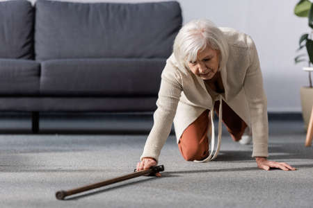 fallen, helpless senior woman trying to get walking stick on floor