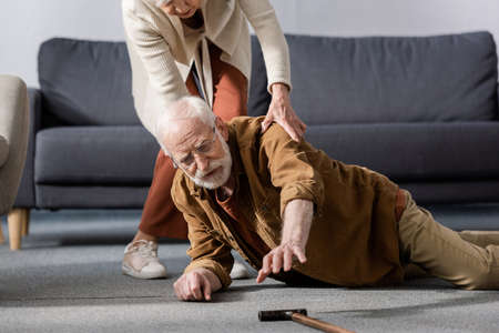 senior man lying on floor and trying to get walking stick while wife helping him
