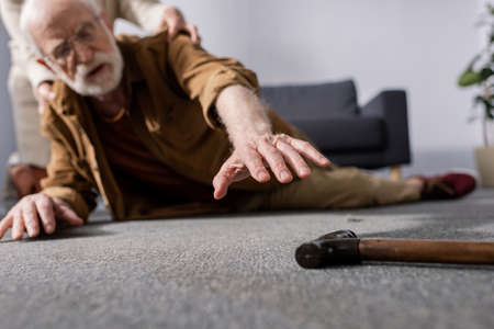 selective focus of fallen senior man trying to get walking stick while wife helping him