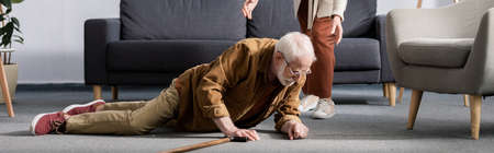 partial view of woman helping fallen senior husband to get up from floor, horizontal concept