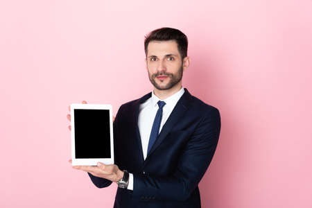 Photo pour handsome businessman holding digital tablet with blank screen on pink - image libre de droit