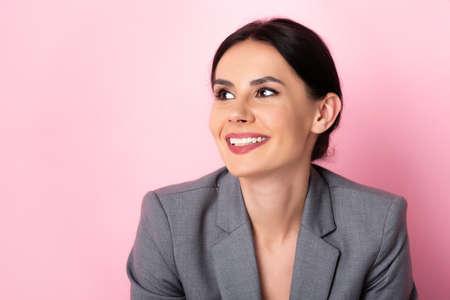 Photo pour happy businesswoman in suit looking away on pink - image libre de droit
